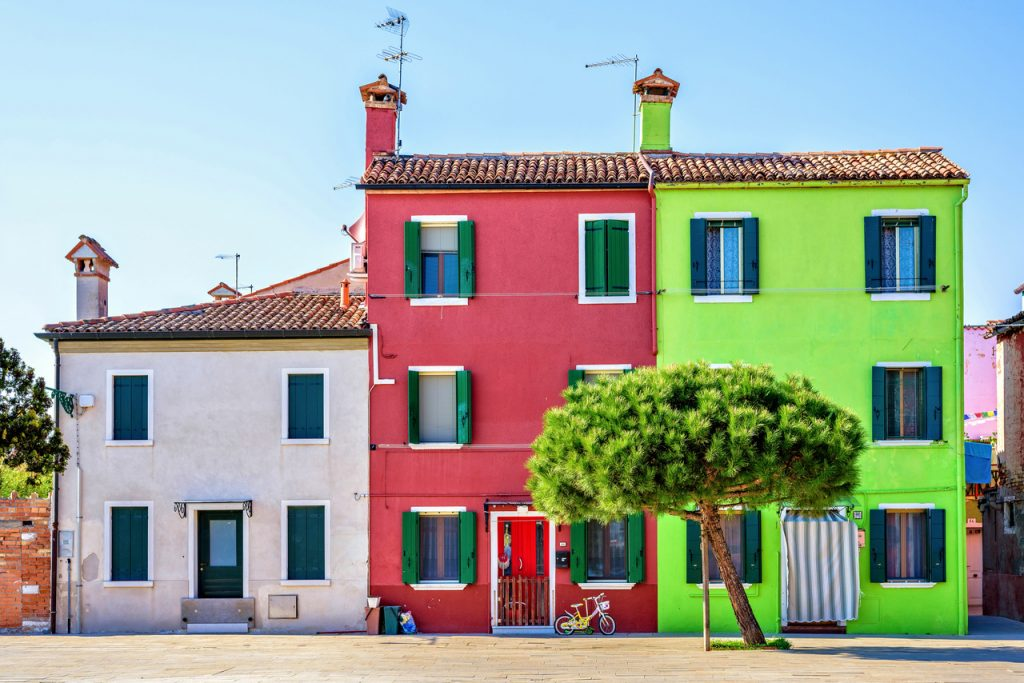 Daylight view to complementary red and green colored buildings with chimney. Cozy and calm atmosphere. Green tree in front. Bright blue clear sky. Negative copy space, place for text. Burano, Italy