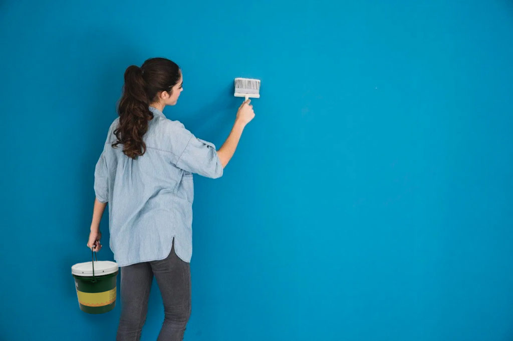 Girl holding a paintbrush in front of a blue wall