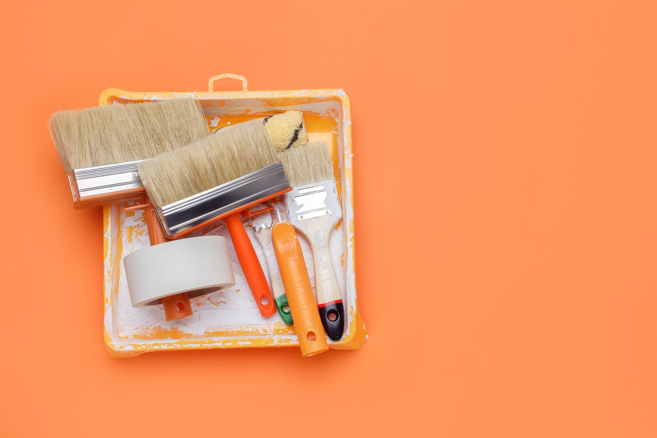 Three paintbrushes and masking tape laid on an orange background