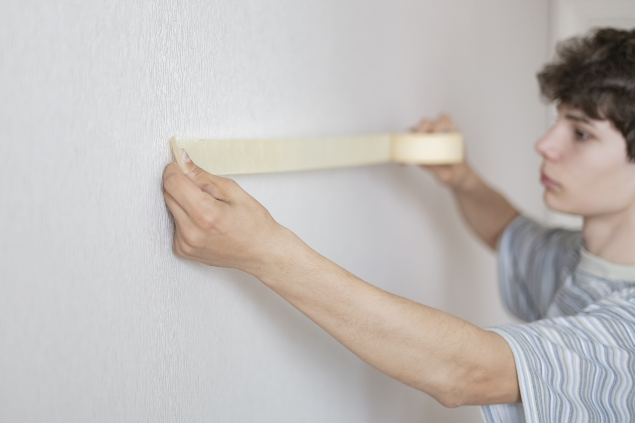 A young man putting masking tape on a wall