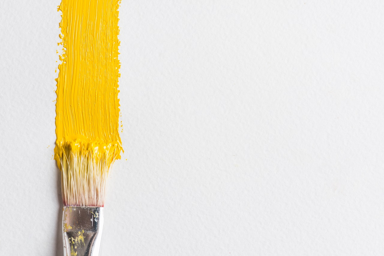 Close up on a brush painting a single stroke of yellow paint on a wall