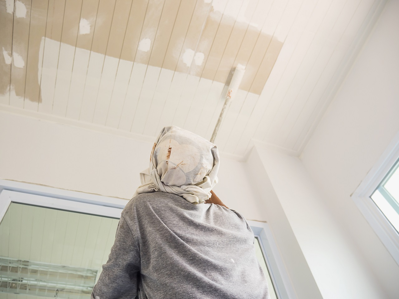 A man painting the ceiling with a long paint roller