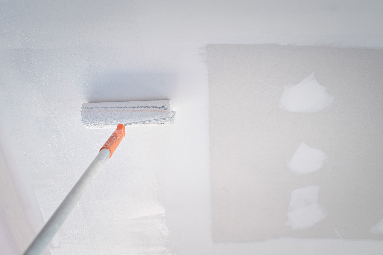 A paint roller painting the ceiling in sections