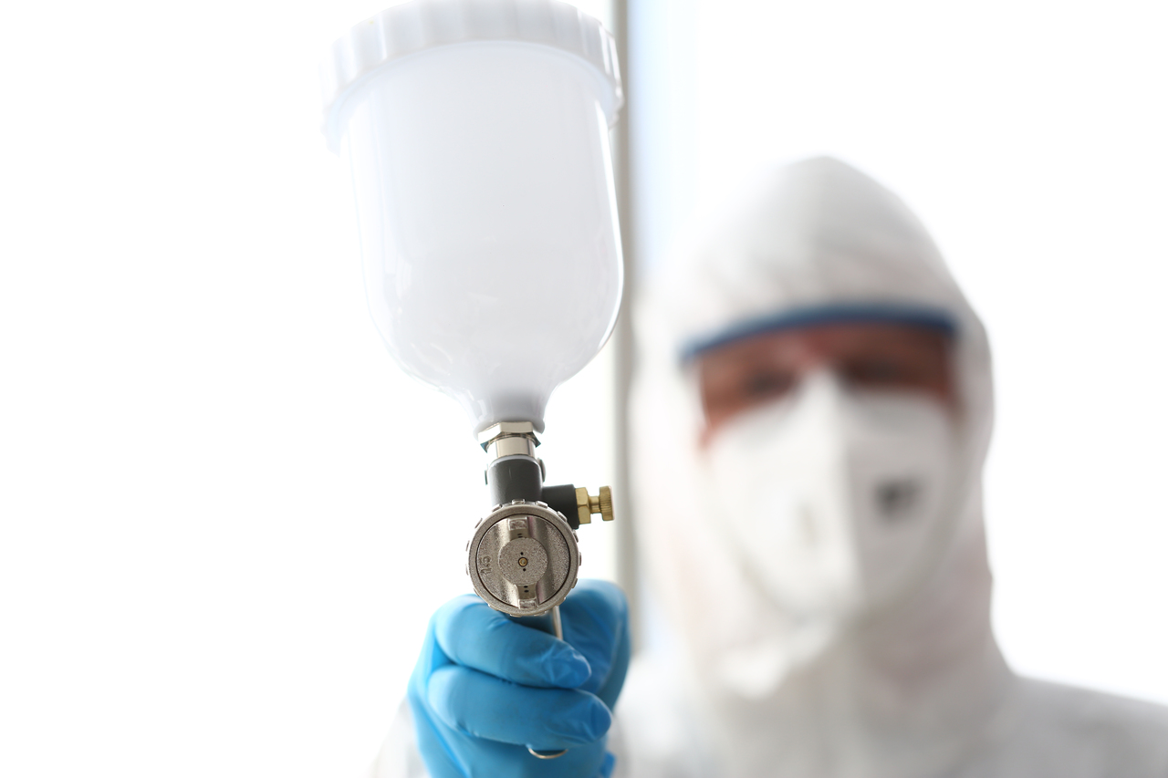 A man in protective gear pointing his paint spray gun