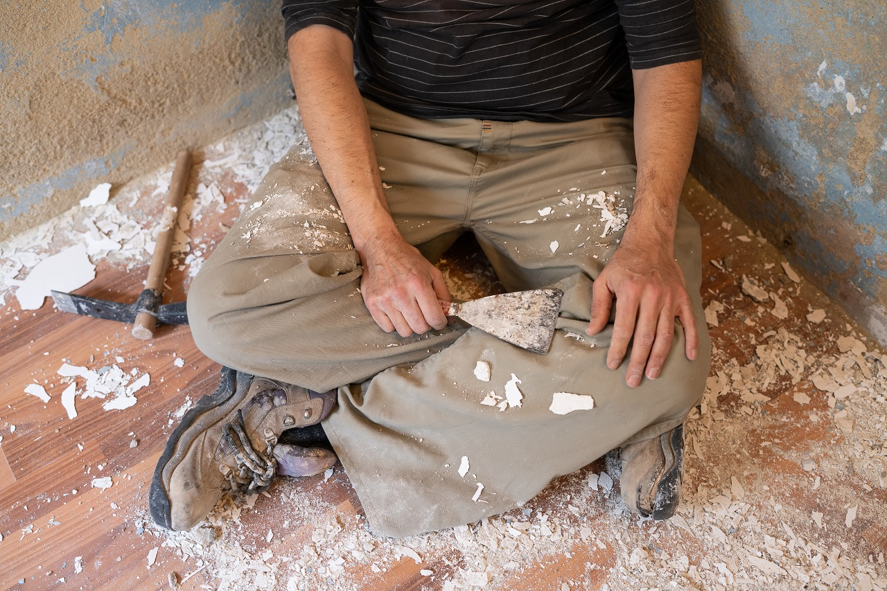 A man resting after removing wall paint using a scraper
