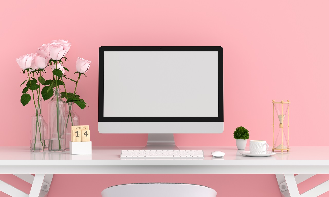 A room with pastel pink walls and a desktop computer